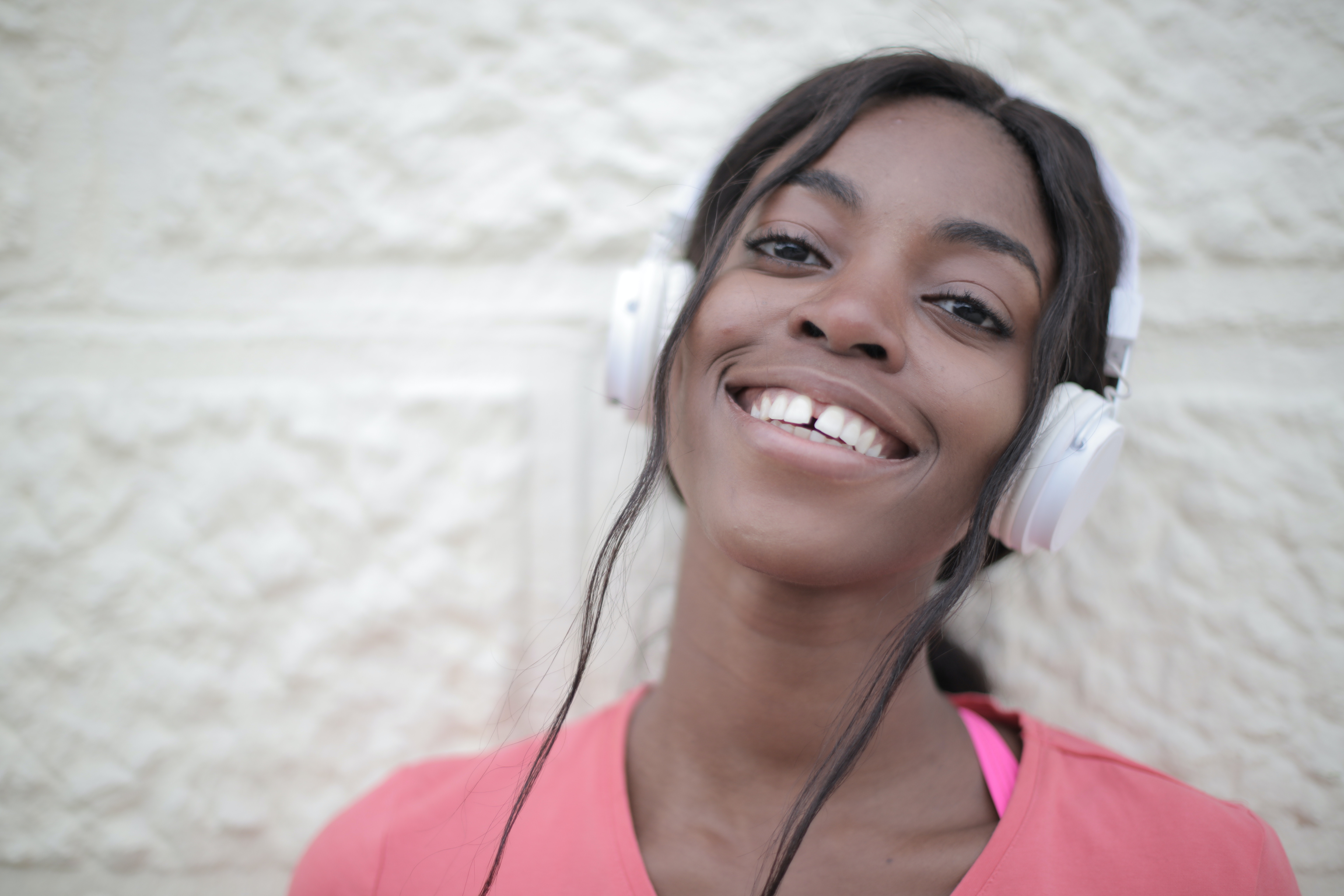 An image of a woman wearing white headphones and smiling at the camera