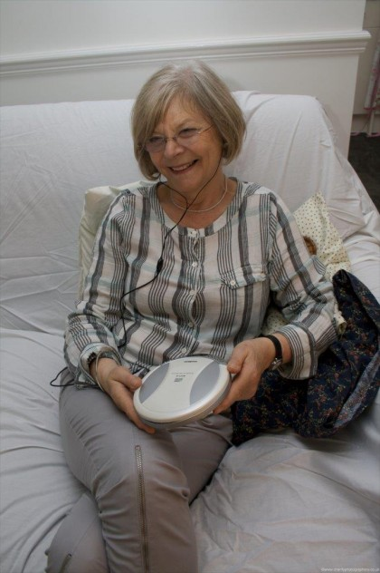 Woman sitting on a white sofa with a CD player on her lap, listening to an audiobook.