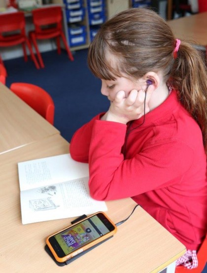 Young girl sitting in a classroom looking a paper book while also listening to it on an MP3 player.