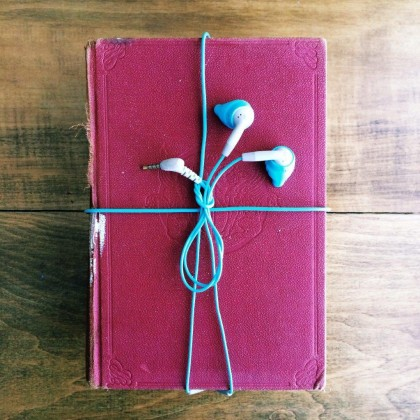 A purple hardback book wrapped with a bow made from earphones, set against a wooden background.