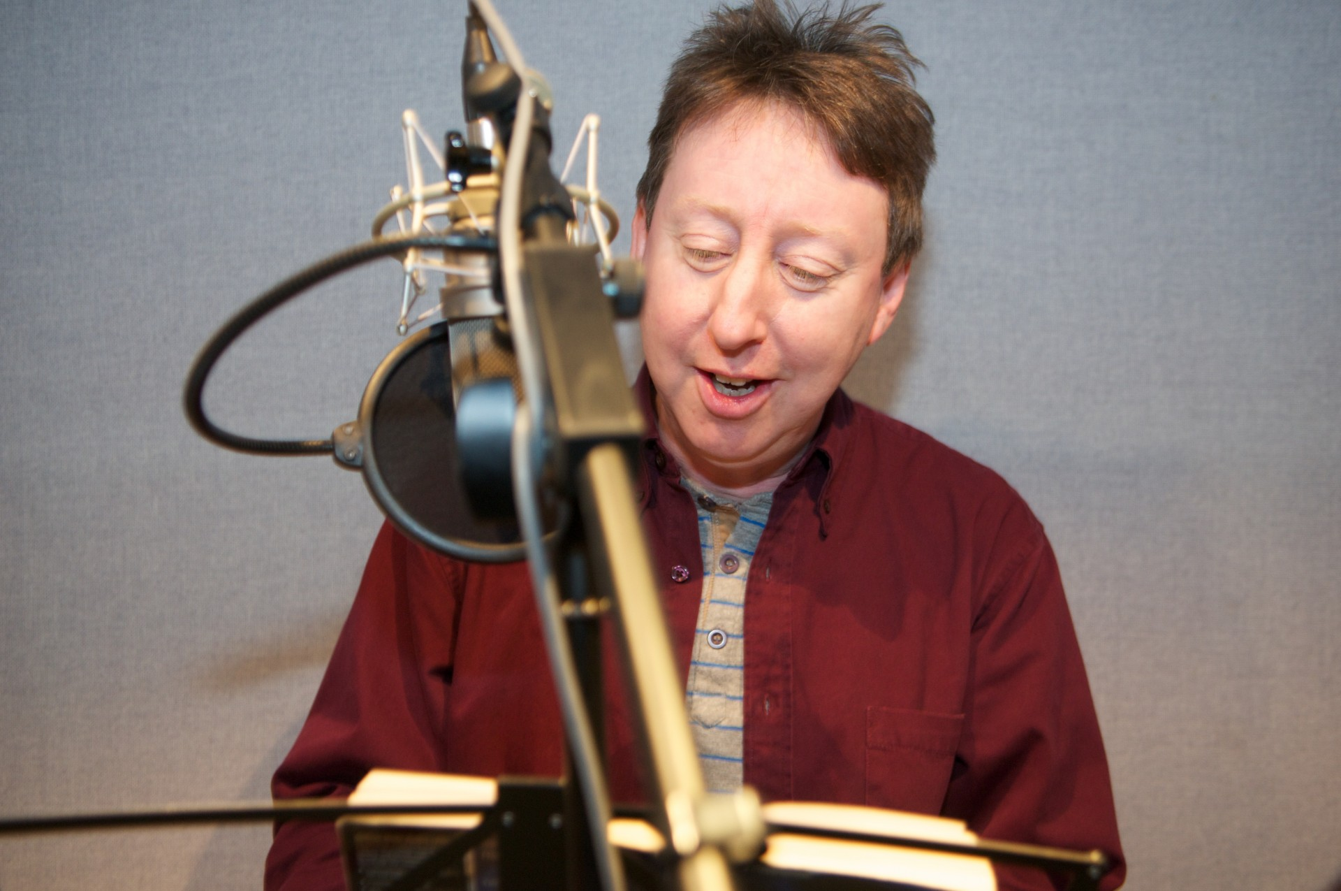 Man facing the camera in front of a microphone.