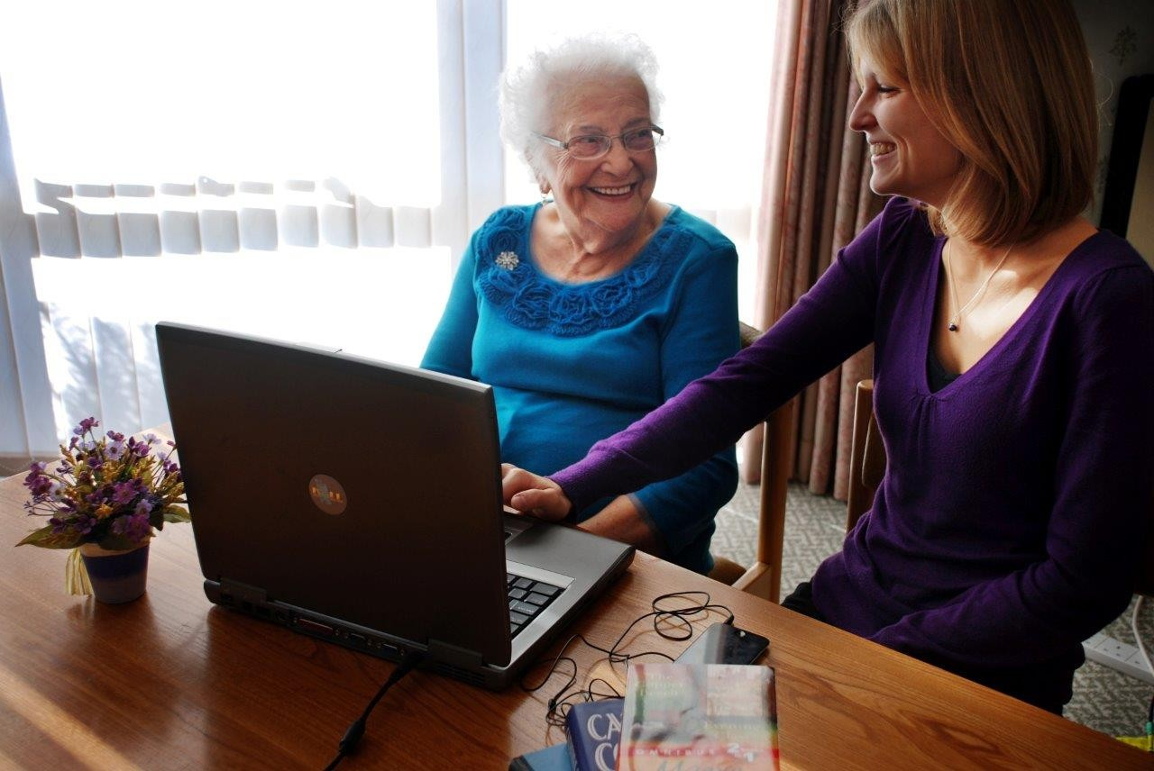 Older person and young person smiling and looking at a computer screen.