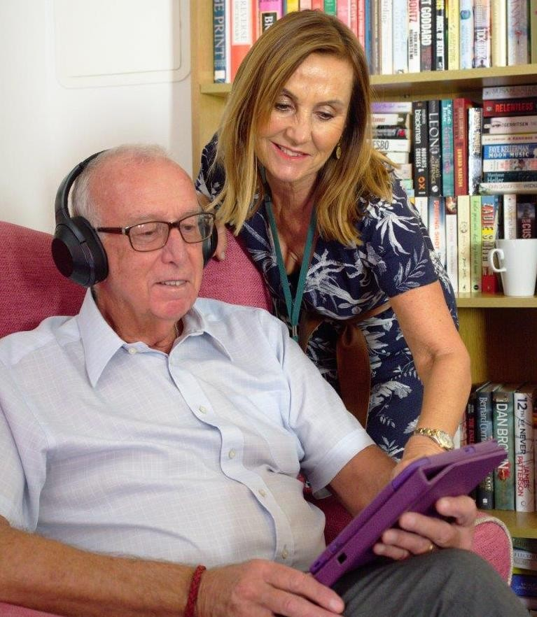 Older man wearing headphones while sitting in a chair. Younger woman looking over his shoulder at the tablet they are using.