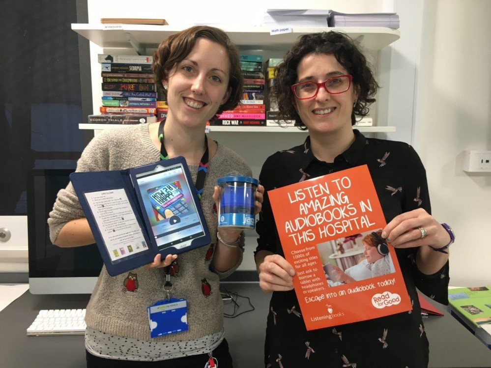 Two women looking at the camera and holding up a tablet and an orange poster.