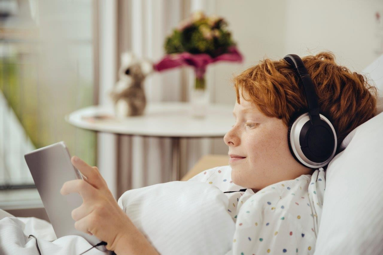 Boy in bed wearing headphones and looking at a tablet.