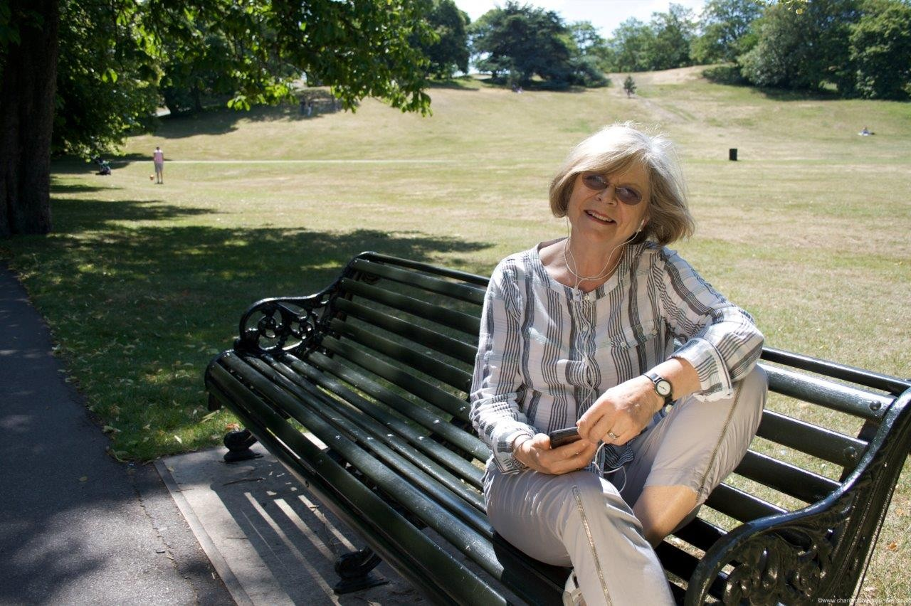 Woman sitting on a bench in a park and smiling while listening to a book on an MP3 player.