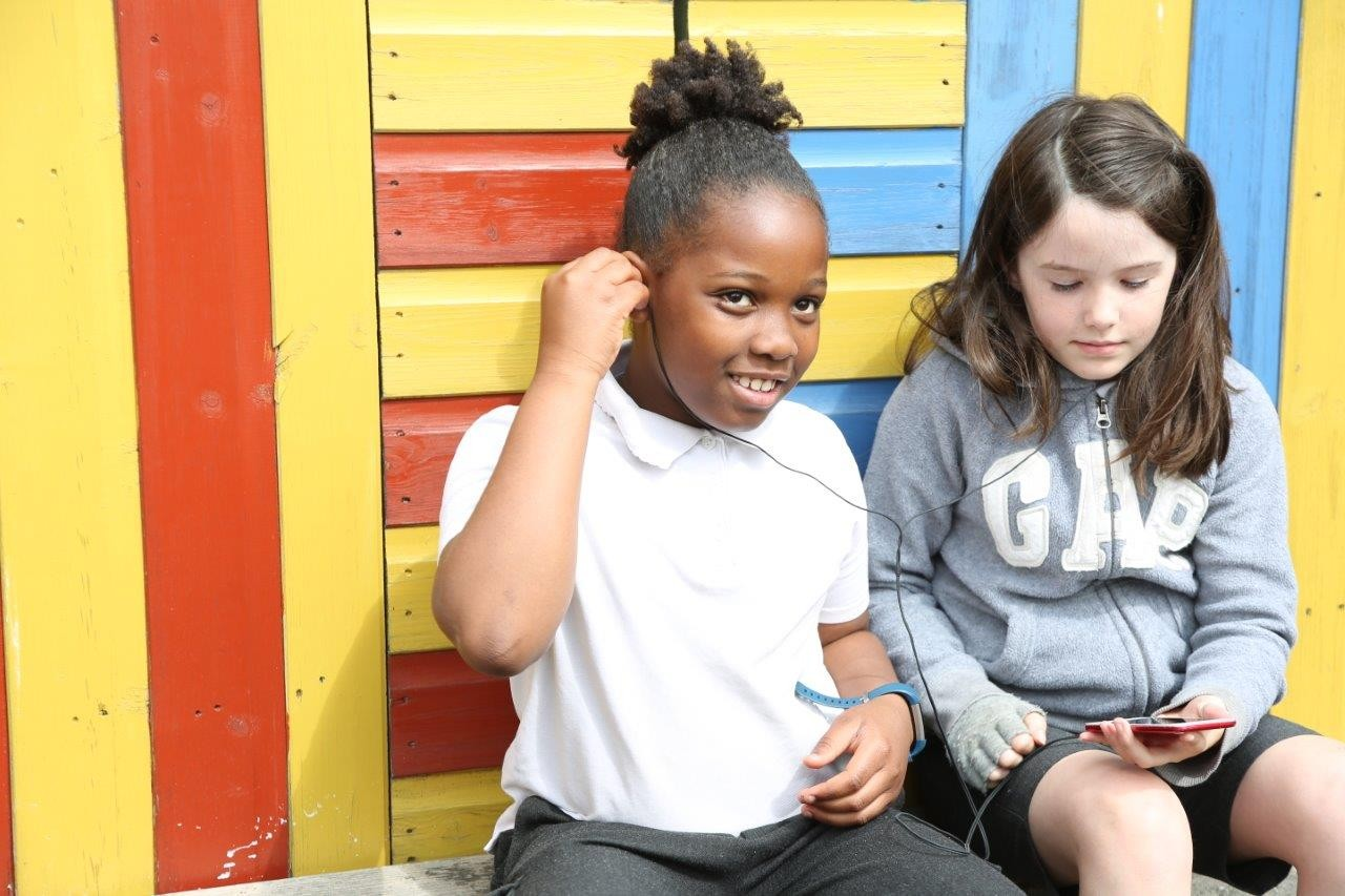 Two children sitting in front of a yellow, red and blue striped wall sharing headphones and looking at an iPod.
