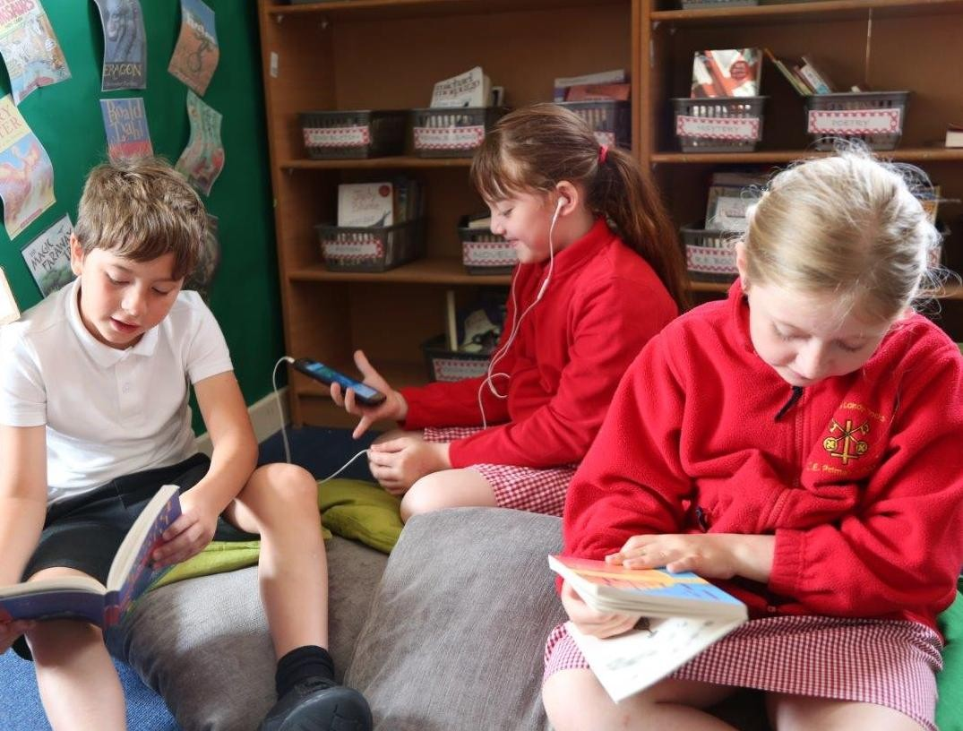 Three children sitting on the floor in a school library. Two children are reading printed books and one is wearing headphones and looking at an iPad.