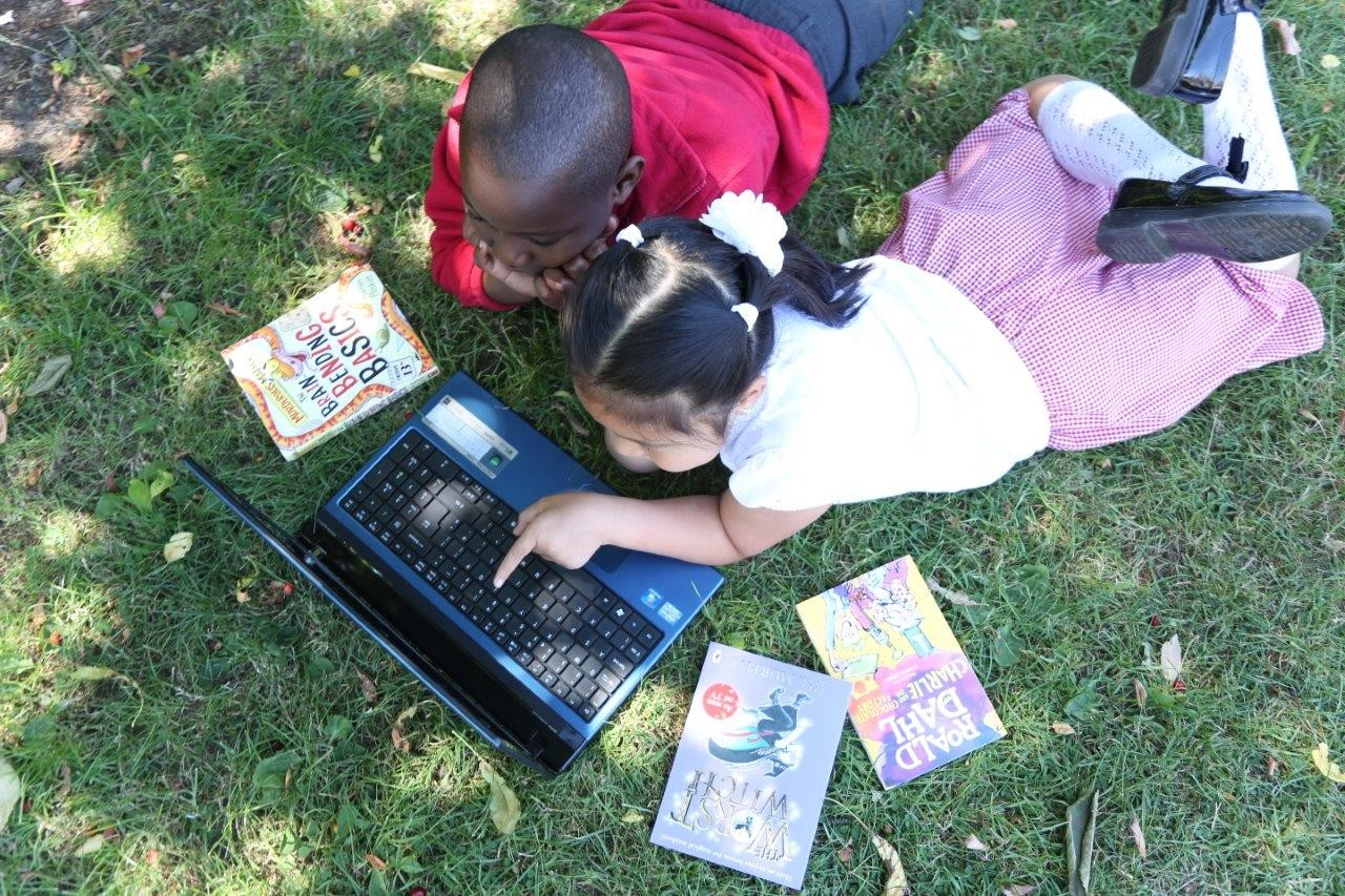Two children lying on grass looking at a laptop surrounded by paperback books.