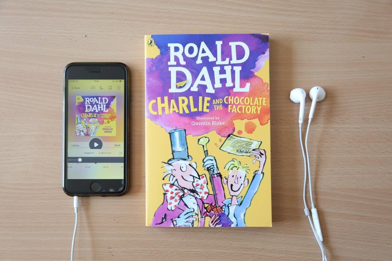 Ipod, paperback book and earphones on a light coloured wood background. The book is Charlie and the Chocolate Factory by Roald Dahl.