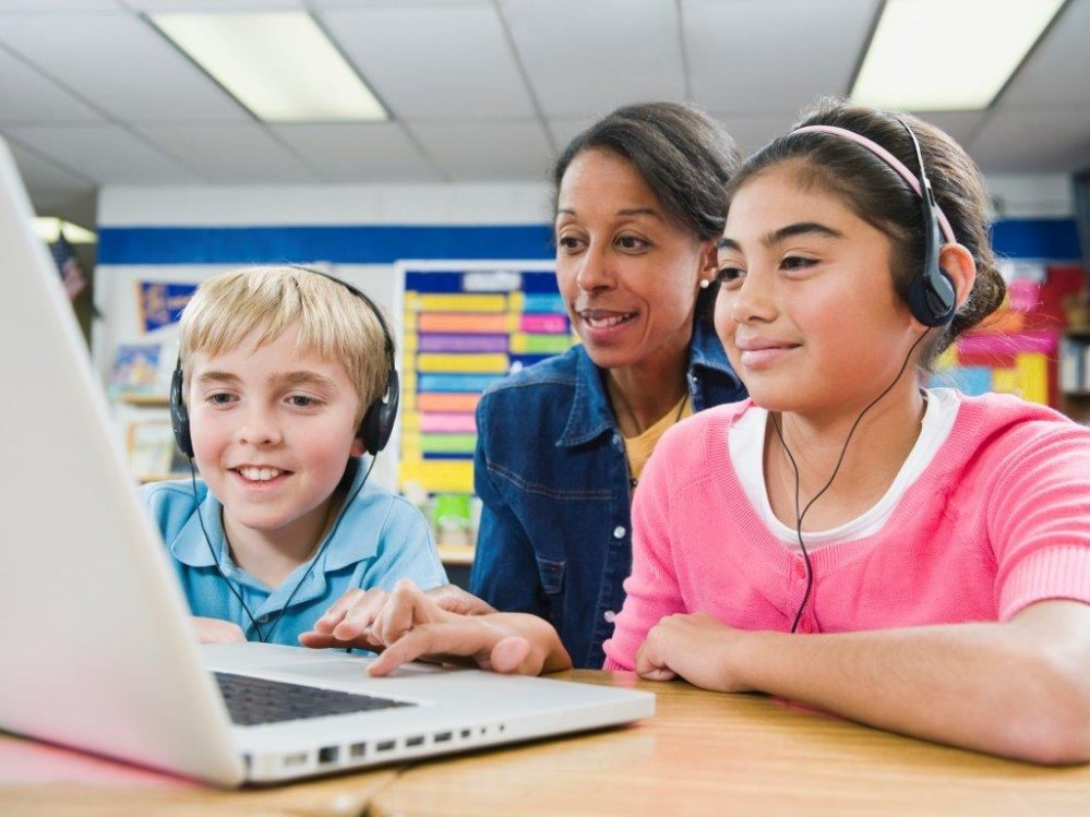 Two children wearing headphones and an adult sitting at a table in a classroom, looking at a laptop.