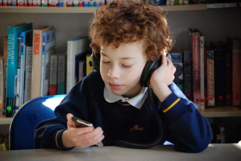 Boy in school uniform sitting in front of a bookshelf, listening to an audiobook through headphones.