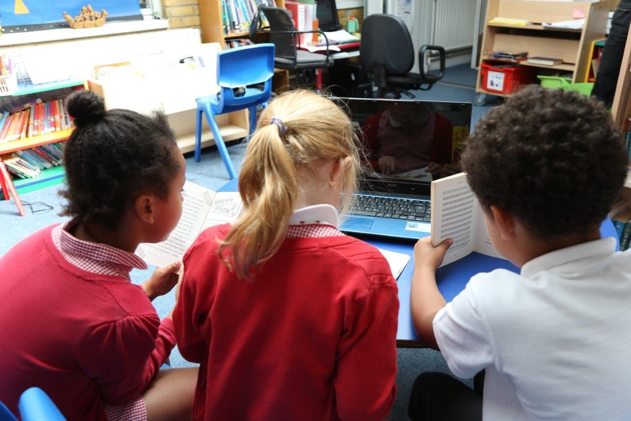 Three children looking at a laptop. One child is reading a printed book.