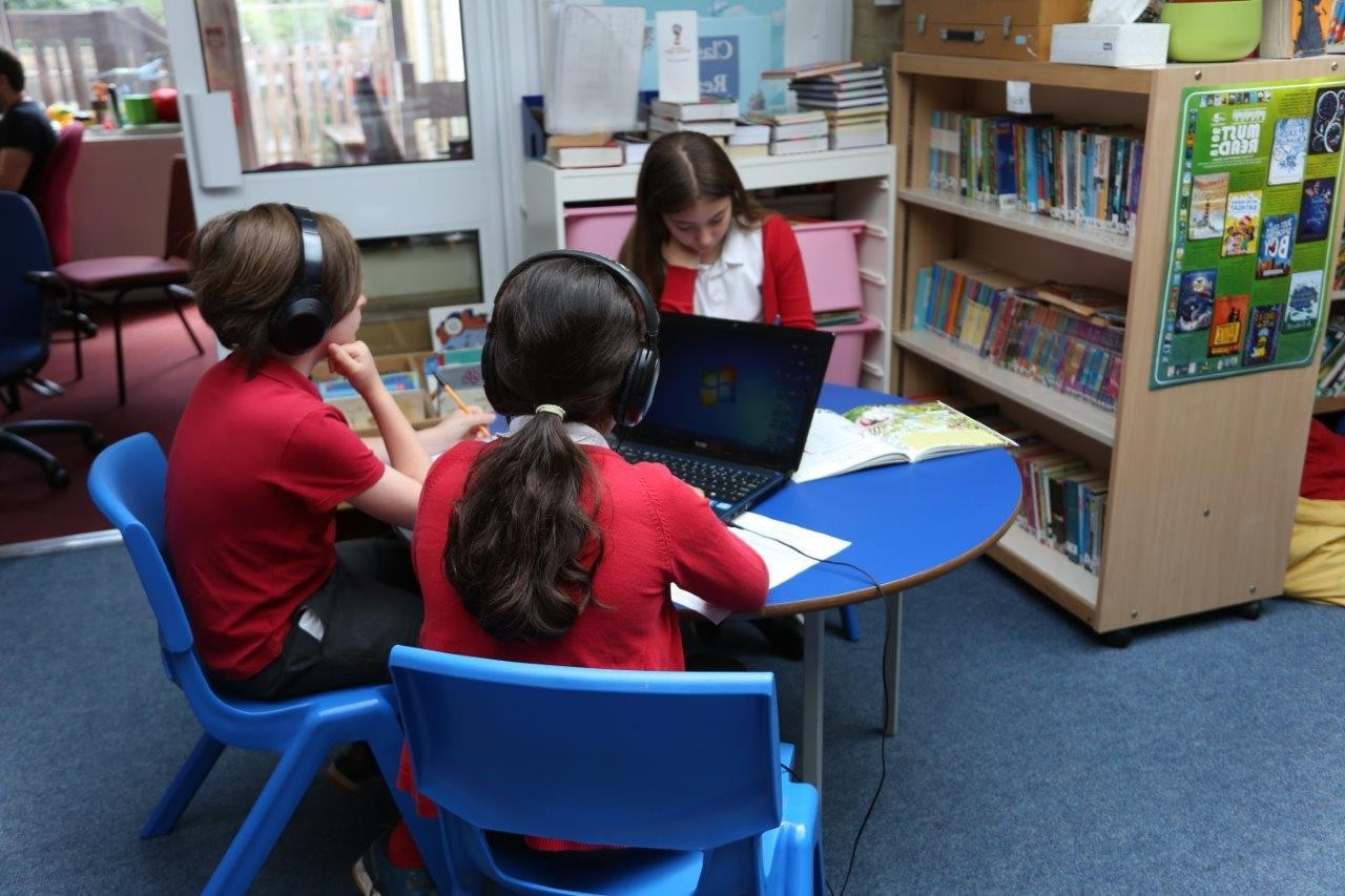 Three children sitting at a round table in a school library listening to books played on a laptop.