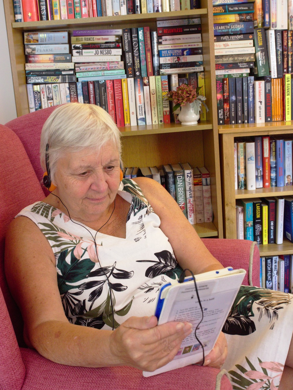 Image of woman looking at a tablet and listening to an audiobook.