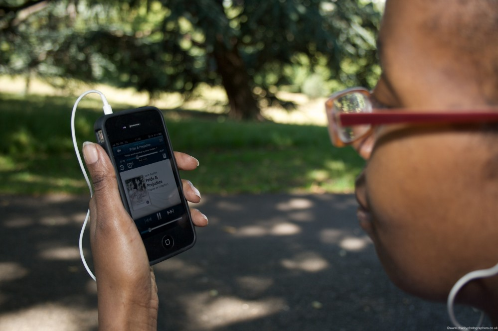 Woman sat in a park, looking at the OverDrive app on an iPhone while listening to a book